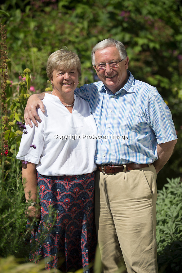 """13/08/16<br /> <br /> Jenny and Anthony Phillips<br /> <br /> """"This is probably the best year ever for our giant gunnera plant,"""" said gardener Jenny Phillips.<br /> <br /> """"The heavy rain followed by a brief heatwave has really made it flourish.<br /> <br /> """"At almost 12 ft tall, with leaves more than 5ft in diameter, it's the biggest I've ever seen.""""<br /> <br /> Jenny and her husband, Anthony, were given their gunnera manicata as a house warming gift, 25 years ago, and since then have watched it grown from a small pot to the giant plant it is today.<br /> <br /> """"It's pretty impressive,"""" said 70-year-old Jenny. """"We've taken lots of cuttings for friends and planted more ourselves and every year it amazes us with its size.""""<br /> <br /> Gunnera, also known as Chilean rhubarb, or giant rhubarb, is native to South America, but thrives in the UK's wet and warm climate, and can usually be found growing along river banks and in marshes. <br /> <br /> Its huge leaves, together with thick, thorny stems, covered in thousands of tiny spines, come to life every spring, dying back to its roots over winter.<br /> <br /> And whatever the British weather, the couple can take advantage of the plant's giant leaves, sheltering beneath them, with a cup of tea and biscuit, in their garden, in Uttoxeter, Staffordshire.<br /> <br /> Jenny, together with husband Anthony, were given their gunnera as a house warming gift, 25 years ago, and since then have watched it grown from a small pot to the giant plant it is today.<br /> <br /> """"It's pretty impressive,"""" said Jenny. """"We've taken lots of cuttings for friends and planted more ourselves and every year it amazes us with its size.""""<br /> <br /> <br /> If you fancy owning your own dinosaur plant, the couple's five-bedroom house, close to Uttoxeter Racecourse is up for sale with agents John German for £950,000.<br /> <br /> All Rights Reserved, F Stop Press Ltd. +44 (0)1773 550665"""