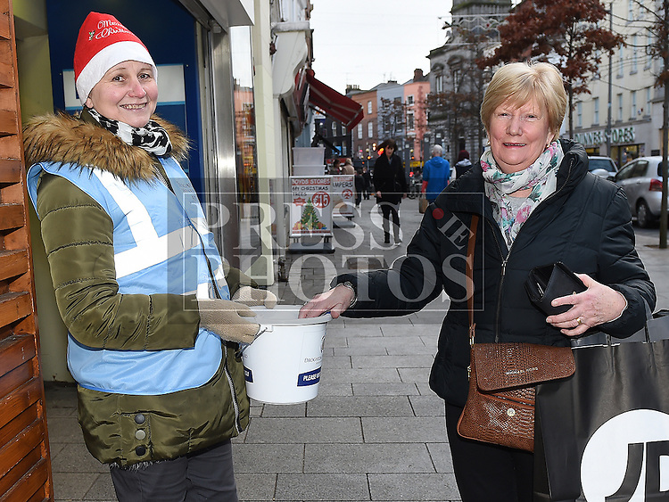 Charlotte McCormackputs a donation in the bucket held by Irena Peckiene at the annual sleepout for Drogheda Homeless Aid. Photo:Colin Bell/pressphotos.ie