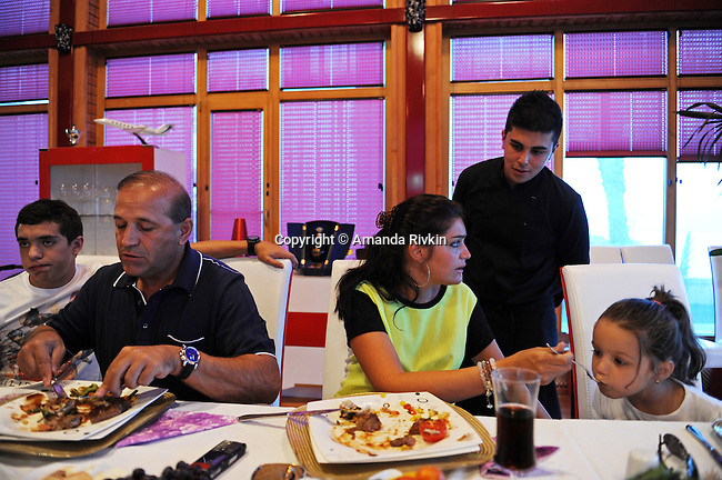 Ibrahim Ibrahimov (second from left) eats dinner with his son Huseyn Ibrahimov, 18, and daughter Ilkana Ibrahimova, 22, and her daughter Cahan Guliyeva, 4 in his home between Sangachal and Sahil, Azerbaijan on August 16, 2012.