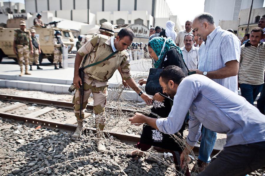 Un officier de l'armée laisse passer une dame qui doit travailler de l'autre côté de la route que l'armée bloque juste avant  le sit-in de Rabaa à Nasr City, Le Caire, Egypte, le mercredi 14 août 2013. La police égyptienne en tenue anti-émeute a balayé à l'aide de véhicules blindés et bulldozers les sit-des partisans du président déchu Mohamed Morsi. Les manifestants ont fait face à des des gaz lacrymogènes ainsi que de coup de feu à balles réelles.