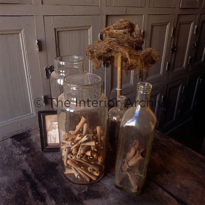 Glass storage jars and bottles are placed on a a dusty table, which stands before a set of painted lockers.