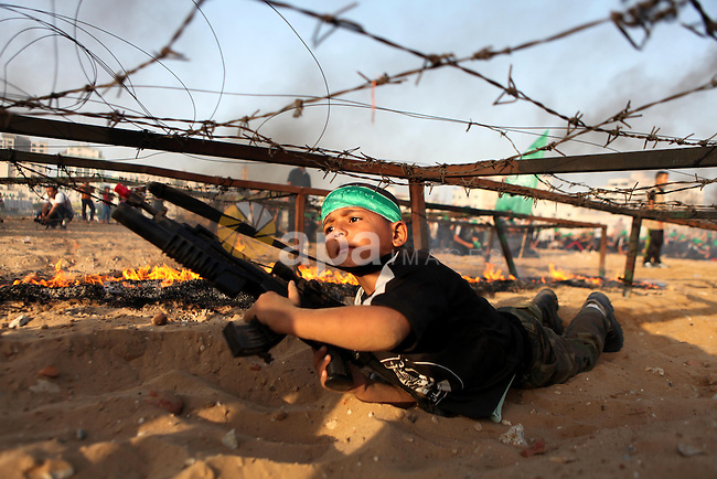 A Palestinian boy demonstrates his skills during a graduation ceremony of a military-style summer camp organized by the Hamas movement in Gaza City June 19, 2014. Hamas stages dozens of military-style summer camps for young Palestinians in the Gaza strip to prepare them to confront any possible Israeli attack, organisers said. Photo by Ezz Zanoun