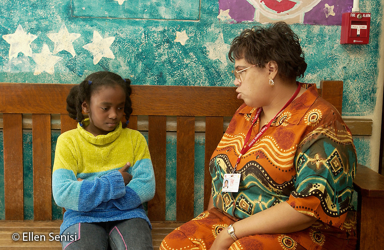 MR / Schenectady, NY.Yates Arts-in-Education Magnet School (urban school, arts theme school).Elementary school principal (African-American and Native American, age 42) and student (girl: 7, Afro-Guyanese) talk about problem on bench in front hallway of school..MR:  Wal7 Sco4.© Ellen B. Senisi