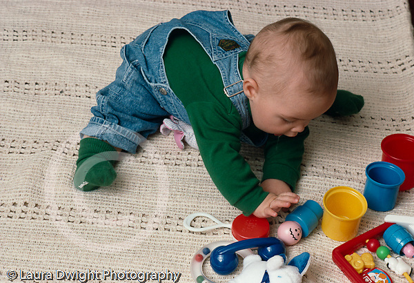 6 month old baby boy sitting, full length, leaning over to grasp toy horizontal