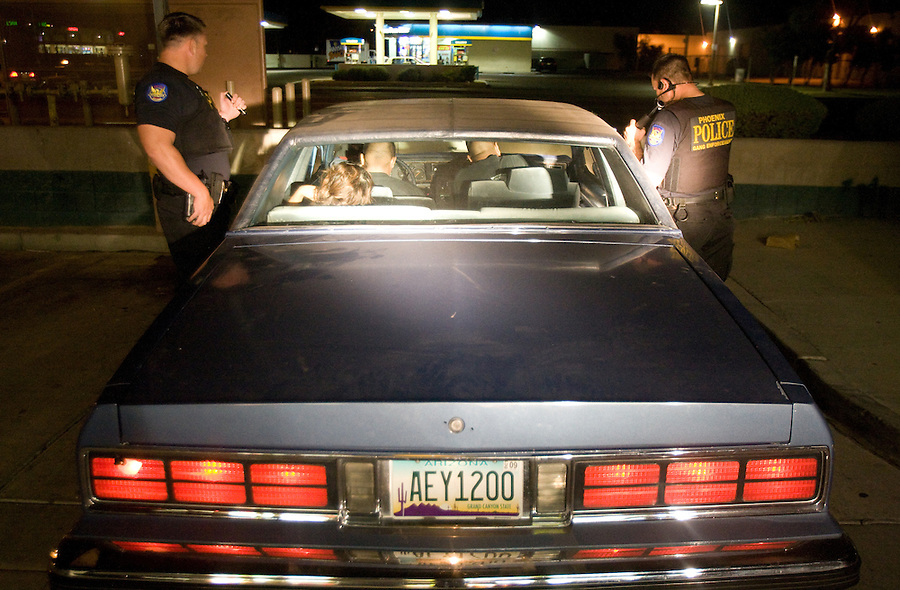 phx-sunnyslope0919 160629-- Phoenix gang detectives Bryan Cuthbertson, left and  T.J. Moore (CQ), right, make a vehicle stop in west Phoeinx. The unit, which focuses on criminal street gangs, also played key roles in other major long-term conspiracy investigations into gang drug violence. The driver was driving on a suspended license. (Pat Shannahan/ The Arizona Republic)