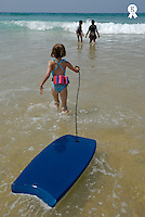 Girl (5-7) walking into surf, pulling float, rear view (Licence this image exclusively with Getty: http://www.gettyimages.com/detail/200503005-001 )