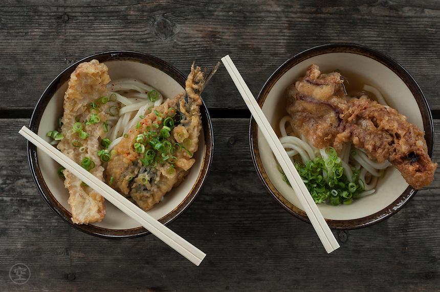 Bowls of noodles topped with tempura (chikuwa, sardine, and calamari) and seasonings at Gamo Udon.