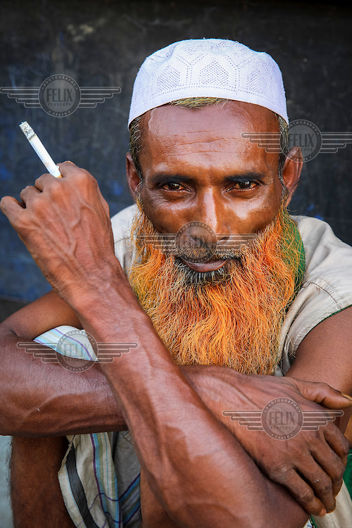 An old man who dyed her hair with Henna.<br /> <br /> It is very common in Bangladesh to see older people with dyed orange hair, men with orange beards or orange moustaches and women with orange hair. The dye used is from the flowering Henna plant. The practice comes from the widely held belief that the Prophet Muhammad dyed his beard and hair. It is also common among people returning from Hajj. Some Muslims believe that henna is the only dye they are free to use for colouring their hair.