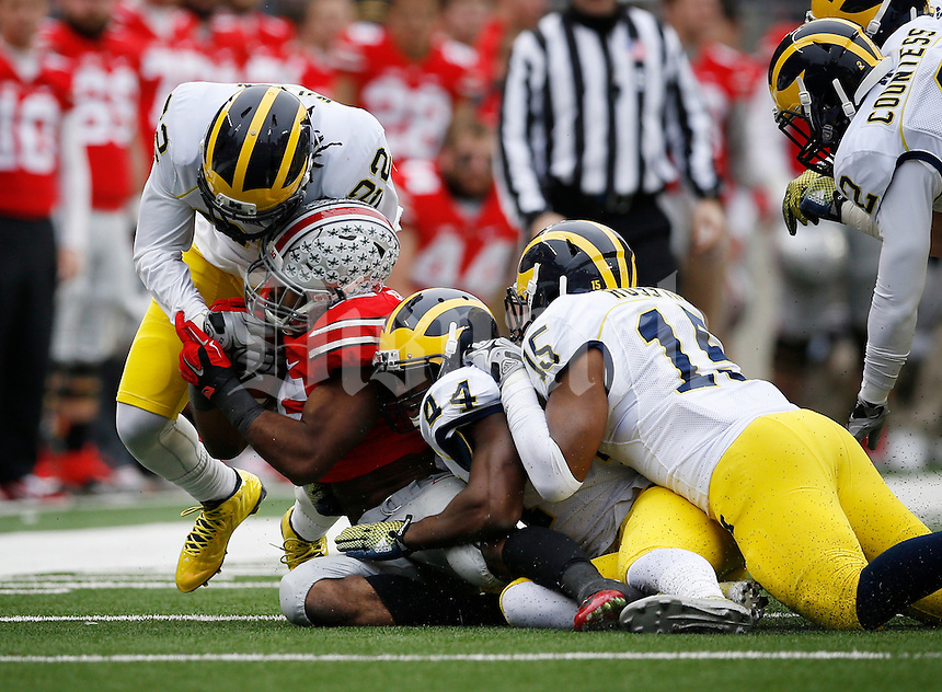 Ohio State Buckeyes running back Ezekiel Elliott (15) gets tackled by Michigan Wolverines safety Jarrod Wilson (22), defensive back Delano Hill (44) and linebacker James Ross III (15) during the 2nd quarter of the NCAA football game at Ohio Stadium on Nov. 29, 2014. (Adam Cairns / The Columbus Dispatch)