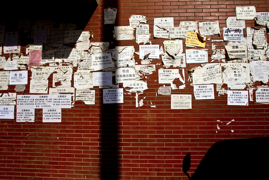 Ads for apartment rentals are plastered on a wall in a new housing development in the new city of Linhe. As many properties are bought as investments, hundreds of thousands of new homes remain empty.