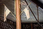 U.S. flags through the window of the old saloon, the ghost town of Bodie, California, State Historic Park.