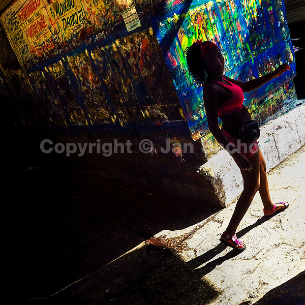A Colombian woman walks along the wall, covered by the Champeta music posters scraps, at the market of Bazurto in Cartagena, Colombia, 15 April 2018.