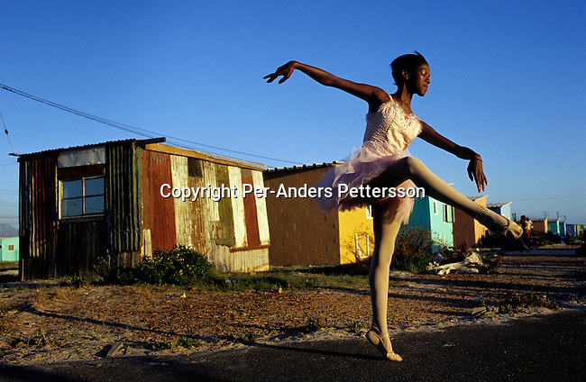 Noluyanda Mqutwana strikes a pose outside her small family house on January 30, 2000 in Khayelitsha, the biggest black township, outside Cape Town, South Africa. Noluyanda is one of about 200 unprivileged children dancing ballet in a program called Dance For All, Many children are talented and the discipline taught during the dance classes has helped many to improve their concentration in school. The township is struggling with high unemployment, crime and high levels of HIV/Aids. (Photo by: Per-Anders Pettersson)