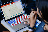 USA, Nebraska, Omaha, Creighton University, Medical Anthropology; Department of Cultural and Social Studies, student with apple notebook with keyboard with american flag