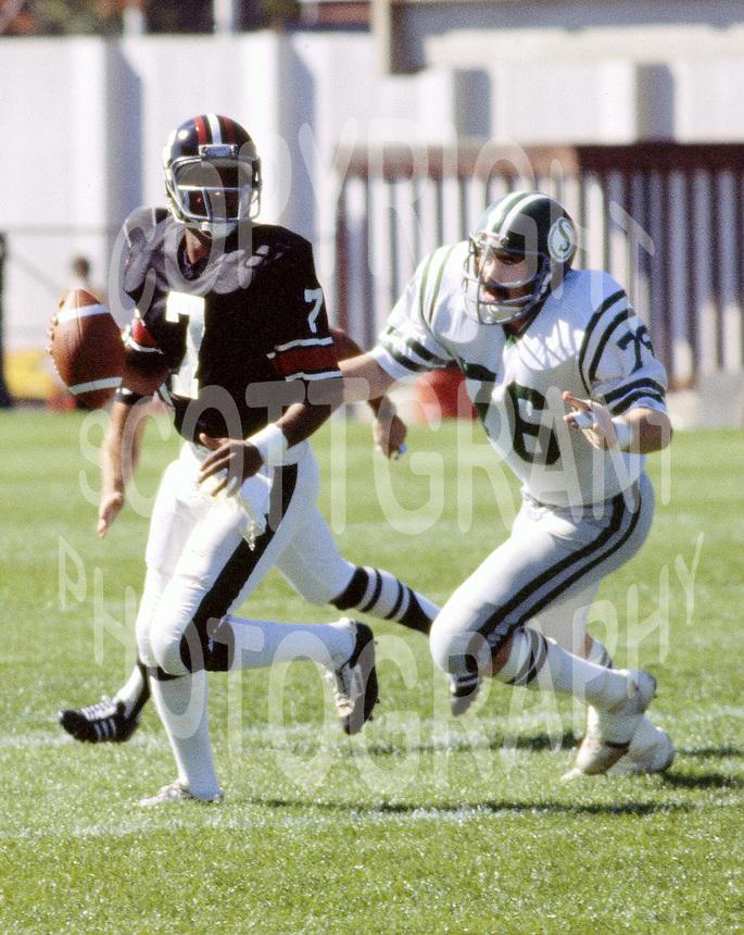 Bill Baker Saskatchewan Roughriders chases Condredge Holloway Ottawa Rough Rider quarterback. 1978 Copyright photograph Scott Grant