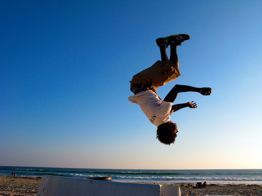 A young man does a backflip into the sand off the sea wall along the boardwalk in the Pacific Beach section of San Diego, California on June 28, 2008.