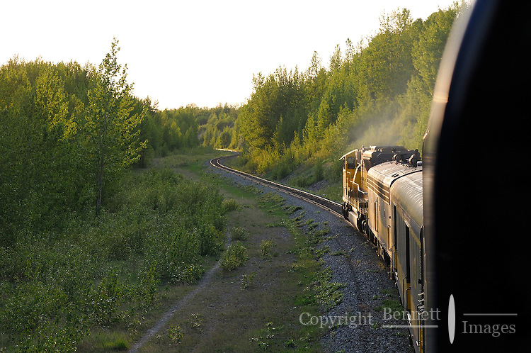 The Alaska Railroad's Coastal Classic train approaches Anchorage as it runs along Turnagain Arm into the evening sun.