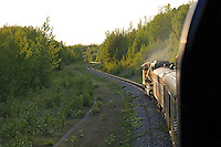The Alaska Railroad's Coastal Classic train approaches Anchorage as it runs along Turnagain Arm into the evening sun.