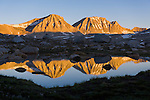 Sunrise on Merriam and Royce Peaks with reflection just below Steelhead Lake in the High Sierra mountains over Pine Creek Pass west of Bishop, California, July 2016.