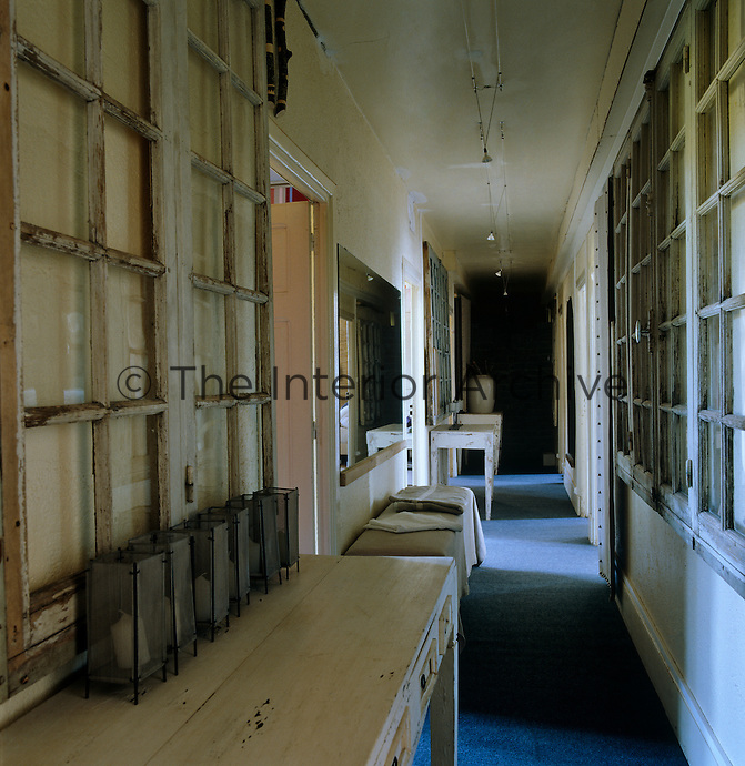 The walls of this corridor are hung with surplus window frames and its narrow width occupied by abandoned tables and stools
