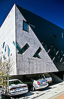 """Distinctive """"black & white floating design"""" for a modern private Tokyo residence set against a blue sky. Showing car park """"illusion"""" underneath."""
