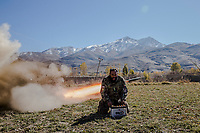 "CHAK VALLEY, WARDAK PROVINCE, AFGHANISTAN - NOVEMBER 11, 2013: Sargeant Sayed Wazir, 40, a former mujahadeen from Khost province, yells ""Allahu Akhbar"" (God is great) as he fires a Russian made BM-12, 107mm rocket, using a car battery, towards Taliban positions in surrounding hills, in the village of Zamankhil where the Taliban has it's district headquarters, on November 11, 2013 in Zamankhil village in the Chak valley, Wardak Province, Afghanistan. 600 ANA soldiers advanced through the Chak valley, a haven for Taliban and insurgent fighters, to re-supply the remote base for the winter. Photo by Daniel Berehulak for the New York Times."
