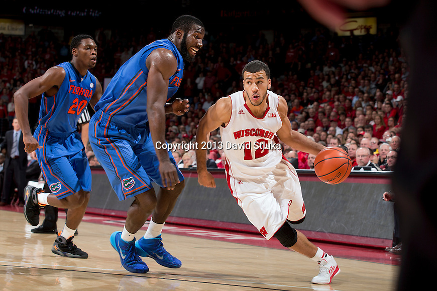 Wisconsin Badgers guard Traevon Jackson (12) drives past Florida Gators center Patric Young (4) during an NCAA college basketball game Tuesday, November 12, 2013, in Madison, Wis. The Badgers won 59-53. (Photo by David Stluka)
