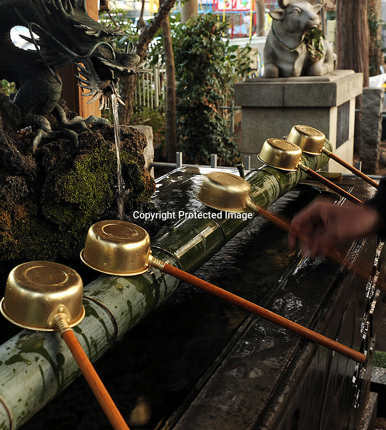 A well for washing hands before entering a shrine in a residential area in Tokyo, Japan.  The Japanese celebrate the first three days of the New Year which are public holidays and days of rest of visits to shrines and temples. The washing of hands before entering a shrine is common in the shinto faith.