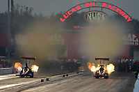 Aug. 31, 2012; Claremont, IN, USA: NHRA top fuel dragster driver Luigi Novelli (right) has a fire alongside Ike Maier during qualifying for the US Nationals at Lucas Oil Raceway. Mandatory Credit: Mark J. Rebilas-
