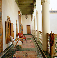 A veranda with a floor tiled in a herringbone pattern looks onto the inner courtyard of the riad