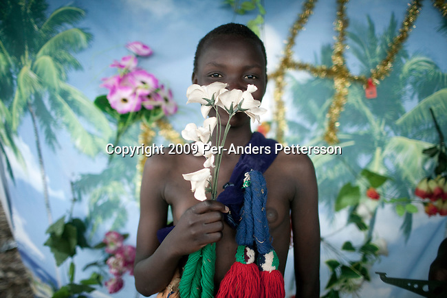 LUDZIDZINI, SWAZILAND - AUGUST 29: A girl poses for pictures in a photo studio before at a traditional Reed dance ceremony at the stadium at the Royal Palace on August 29, 2009, in Ludzidzini, Swaziland. About 80.000 virgins from all over the country attended this yearly event, which goes on for a week and the biggest in Swazi culture. It was founded to celebrate the beauty of Swazi women and girls. King Mswati III, and absolute monarch, was born in 1968 and he has 14 wives and many children. The king danced with his men in front of the 80.000 girls. Many of the girls hope to get noticed by the king and to be chosen as a future wife, a ticket from poverty and into a life of privilege and luxury. The country is one of the poorest in the world and it is struggling with a high prevalence of HIV-Aids and severe poverty. (Photo by: Per-Anders Pettersson)...