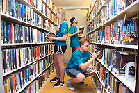 Rebecca Shaub,'21, Shane Gardiner,'21, and Andrew Farnsworth,'21, front, organize books at the Redwood Library as they participate in the Salve Regina University Exploration Day of Service in Newport.