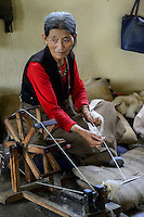 NEPAL Kathmandu, Lalitpur, tibetan refugee camp Jawalakhel, carpet factory JHC Jawalakhel Handicraft Center, tibetan women spin wool for carpets for income generation, wooden spinning wheel the symbol of Mahatma Gandhi struggle for self-determination /  tibetische Fluechtlinge, tibetisches Fluechtlingslager Jawalakhel, Teppichfabrik JHC Jawalakhel Handicraft Center, tibetische Frauen spinnen die Wolle