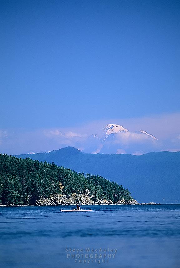 Sea kayaking in the San Juan Islands of Washington State with Mount Baker visible in background