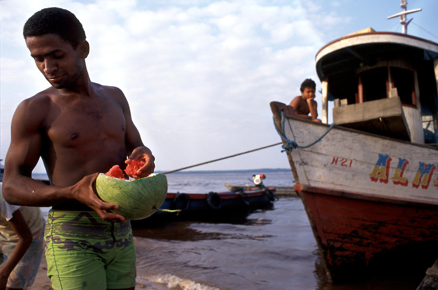 Grabbing a handful of ripe watermelon, a man from Manaus joins others in eating melons tossed into the river by a boat crew. The rejected melons had cracked enroute to the city on the Brazilian Amazon.