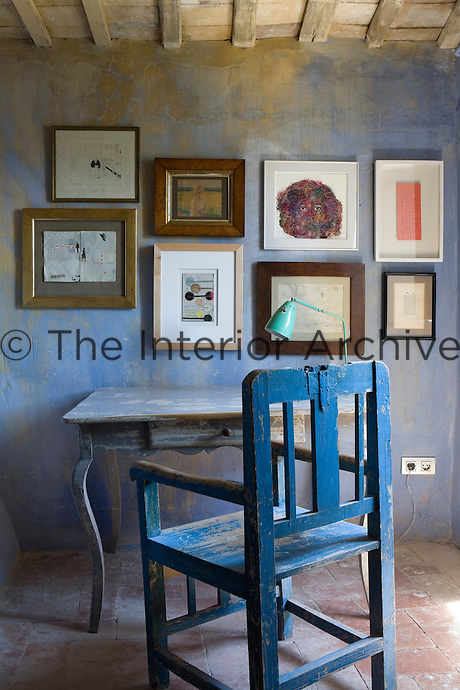 A display of artwork is arranged on the wall above a simple blue painted table and chair in a corner of a rustic blue bedroom.