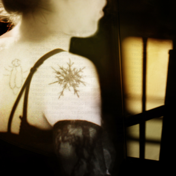 young woman with tattoos and lace  glancing down at a glowing doorway