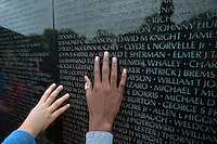 Hands touch the names on the Vietnam Memorial in Washington DC.