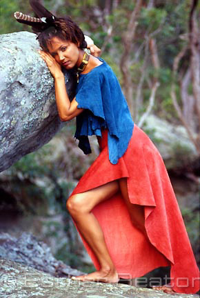 Model of African-American heritage modeling New Age top and skirt made of suede in bushlands north of Sydney, NSW.