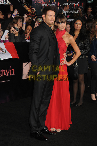 Kellan Lutz and Sharni Vinson .The Los Angeles premiere of 'The Twilight Saga Breaking Dawn Part 1' at Nokia Theatre at L.A. Live in Los Angeles, California, USA..November 14th, 2011.full length black suit side red dress halterneck sleeveless hand on hip couple.CAP/ADM/BP.©Byron Purvis/AdMedia/Capital Pictures.