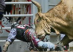 MICHAEL SMITH/WTE ..Bull rider Johnny Chavez is chased down by a bull during rodeo action Sunday at Frontier Park.