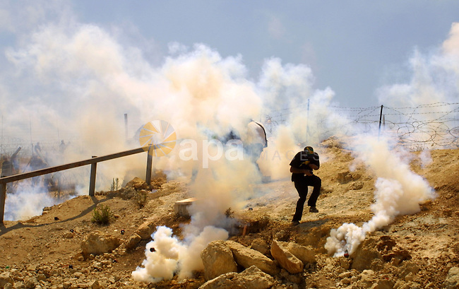 Palestinian and foreign protestors run away from  tear gas threw by Israeli soldiers during a demonstration against Israel's controversial separation barrier in the West Bank village of Bilin near Ramallah on Aug 7, 2009. Photo by Nedal Shtieh