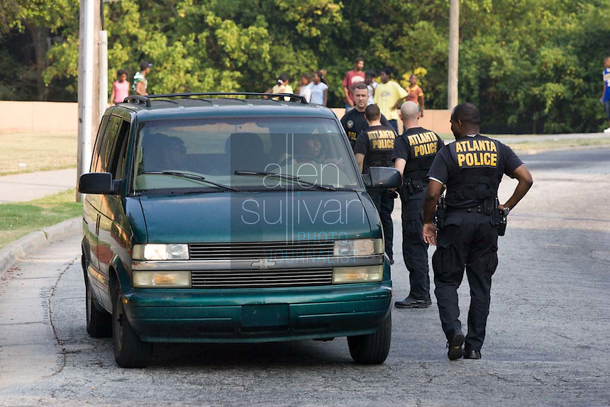 Atlanta Police Department officers check the identification of drivers during sweeps in the Bowen Homes public housing project on Saturday, August 18, 2007. Police said they found drugs, drug money and at least one stolen car during the sweeps, which also included Vine City Terrace Apartments.
