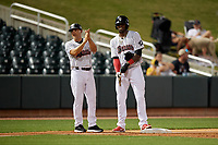 Birmingham Barons manager Omar Vizquel (13) talks with Luis Robert (26) after he hitting a triple during a Southern League game against the Chattanooga Lookouts on May 1, 2019 at Regions Field in Birmingham, Alabama.  Chattanooga defeated Birmingham 5-0.  (Mike Janes/Four Seam Images)