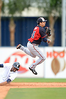 Atlanta Braves shortstop Ramiro Pena (14) turns a double play as Austin Jackson slides in during a spring training game against the Detroit Tigers on February 27, 2014 at Joker Marchant Stadium in Lakeland, Florida.  Detroit defeated Atlanta 5-2.  (Mike Janes/Four Seam Images)