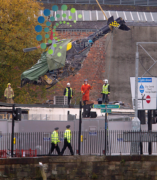 Rescuers have removed a helicopter which crashed into a busy Glasgow pub killing at least nine people.<br /> The wreckage of the Police Scotland aircraft was winched from The Clutha, where it came down at 22:25 on Friday.<br /> Police Scotland have said they cannot rule out finding more bodies.<br /> The three helicopter crew died in the incident along with six people inside the pub. Police have released the names of five of the victims. Efforts to identify other fatalities continue.<br /> Samuel McGhee, 56, of Glasgow, is the second of six people who died in the bar to be named. The three helicopter crew members were named on Sunday. <br /> Picture: Maurice McDonald/Universal News And Sport (Europe) 2 December  2013