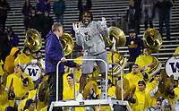 Lavon Coleman, walking boot and all, celebrates the Apple Cup win with the Husky Band after the game.