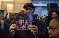 NEW YORK APRIL 21: A man holds a CD Case with the image of Prince at a makeshift memorial place created outside Apollo Theatre in Harlem, New York City, Friday, April 21, 2016. The pop star die a few hours ago at the age of 57.Photo by VIEWpress/Maite H. Mateo