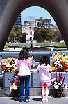Two girls say a prayer in front of the Peace Memorial and, in the distance, the A-Bomb Dome in Hiroshima, Japan.