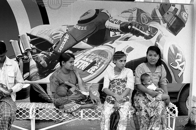 Women wait with children at a bus stop in the city centre, in front of a billboard featuring a motobike advertising imported Lucky Strike cigarettes..